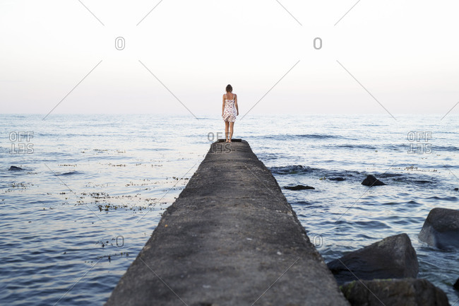 Young woman standing at the edge of a jetty looking out over the ocean