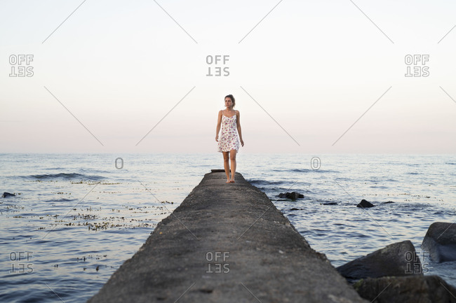 Young woman wearing sundress walking on jetty surrounded by the ocean