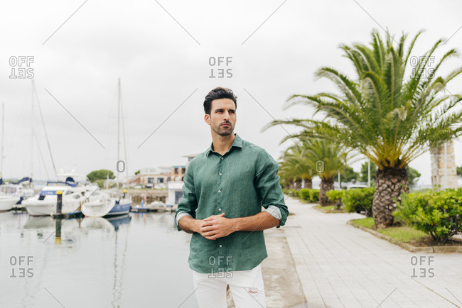 Attractive young man standing on the seafront