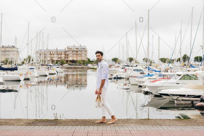 Handsome and stylish man walking barefoot next to the dock