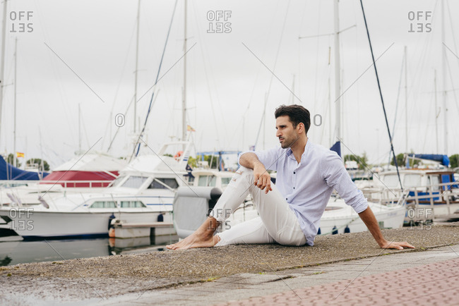 Handsome and stylish man sitting on the dock