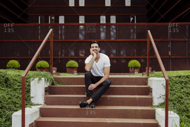 Handsome and stylish man sitting on stairs out of office building