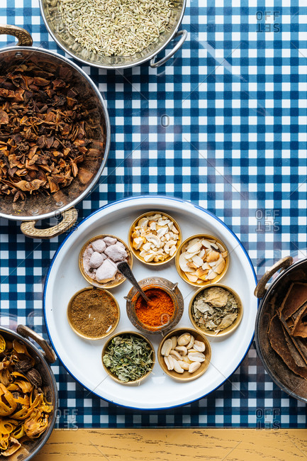 Overhead view of Indian spices and herbs on a checkered background