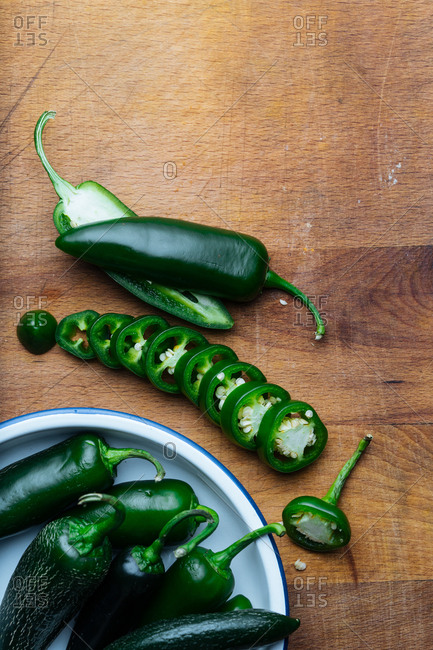 Fresh jalapenos whole and sliced on a cutting board
