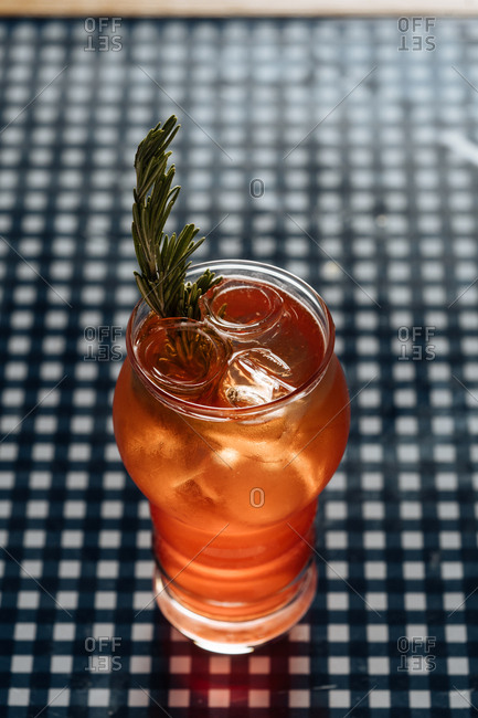 Orange cocktail with rosemary on checkered table