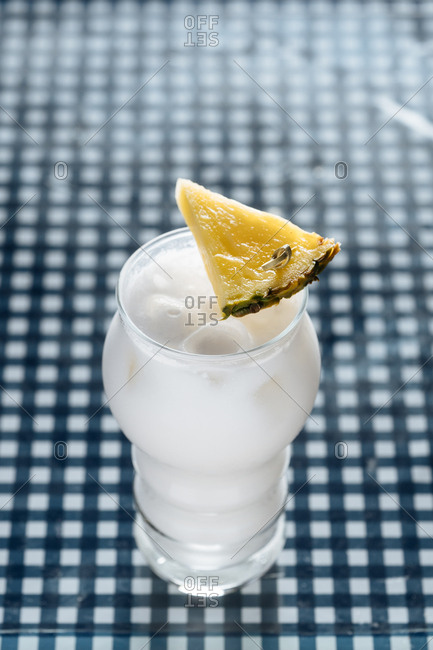 Cocktail garnished with pineapple on checkered table