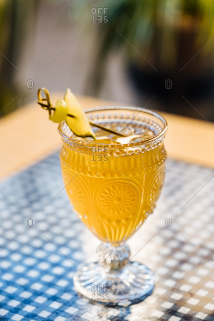 Yellow cocktail garnished with a lime