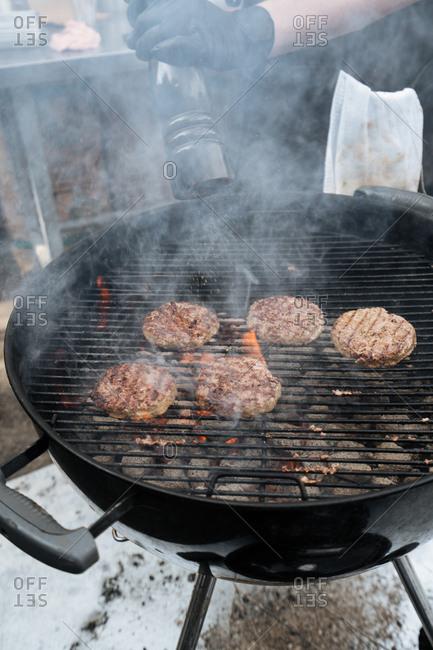 Chef seasoning hamburgers on a charcoal grill