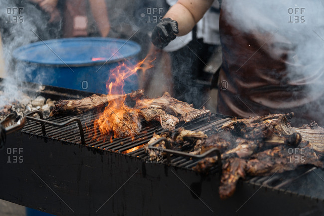 Chef preparing meat on an outdoor grill