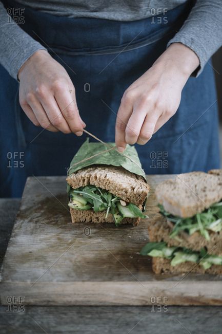 Midsection of woman making sandwich on cutting board at home