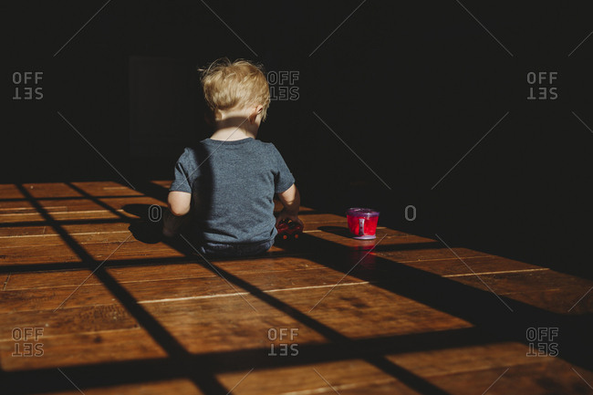 Rear view of baby boy with cup sitting in darkroom at home