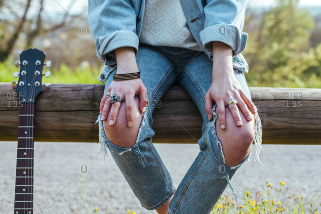 Midsection of woman with guitar wearing torn jeans while sitting on wooden railing against lake at park