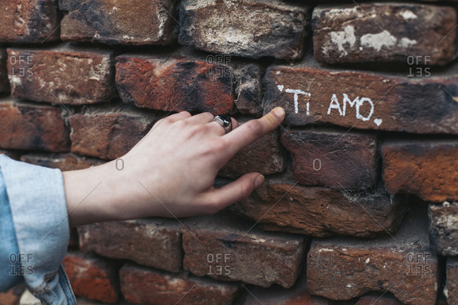 Cropped hand of woman showing text on brick wall