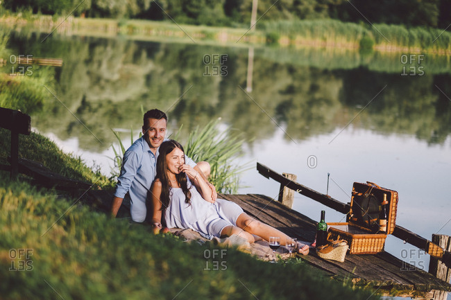 Happy couple relaxing on pier by lake at park