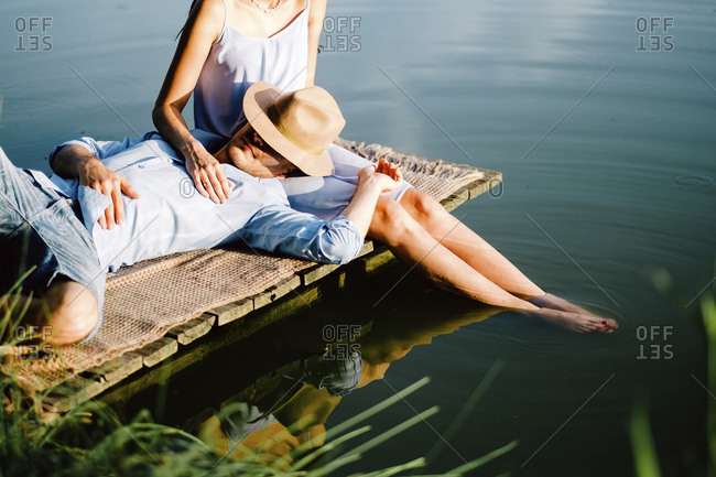 Boyfriend relaxing on girlfriend's lap by lake at park