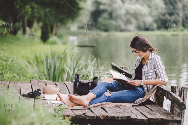 Woman reading book while sitting on pier against lake in forest