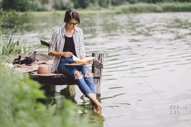 Woman reading book while sitting on pier over lake in forest