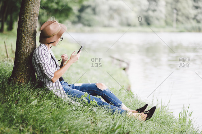 Woman using mobile phone while sitting on grassy field at lakeshore in forest