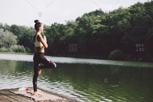 Side view of woman meditating while standing on pier over lake in forest