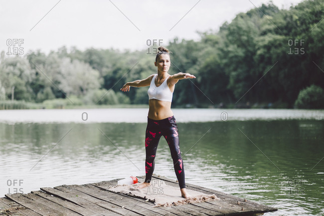 Woman practicing warrior 2 pose while standing on pier over lake in forest