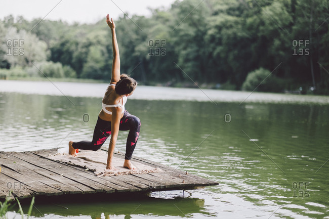 Woman practicing yoga on pier over lake in forest