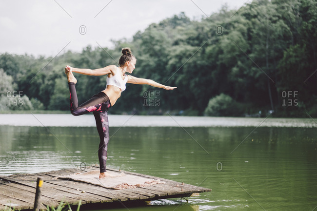 Woman practicing yoga while standing on pier over lake in forest