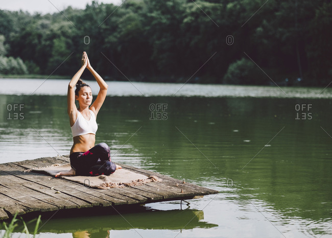 Woman with arms raised meditating while sitting on pier over lake in forest