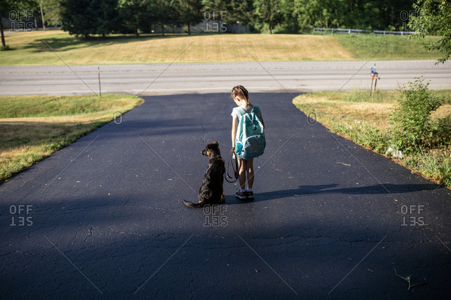 Rear view of girl carrying backpack while standing with dog on road
