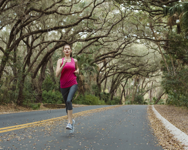 Woman jogging on road amidst trees in forest
