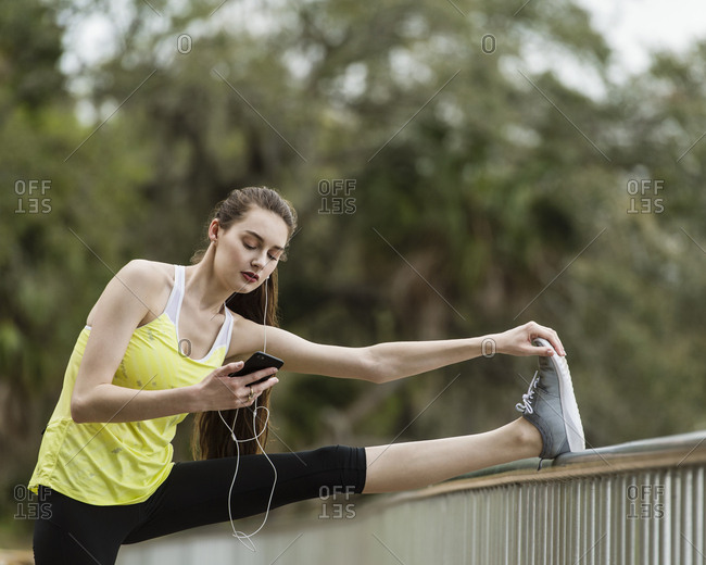 Confident woman using mobile phone while exercising at park