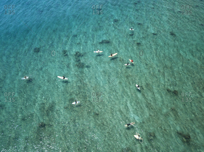 Aerial view of people surfing on sea during sunny day