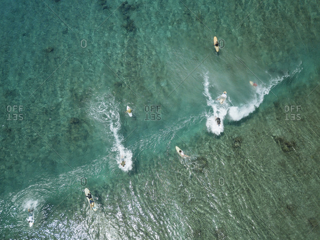 Aerial view of people surfing on sea at Maldives during sunny day