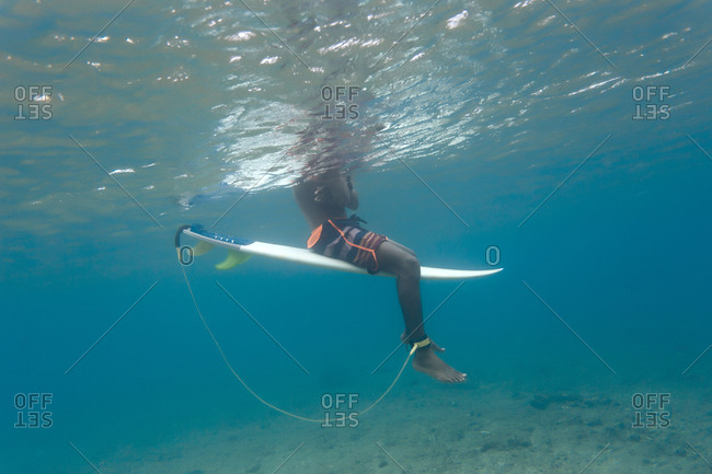 Low section of man surfing in sea at Maldives