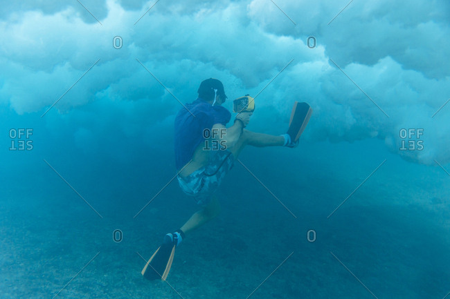 Man holding camera while swimming undersea