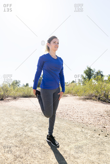 Female hiker exercising while standing on field against clear sky during sunny day