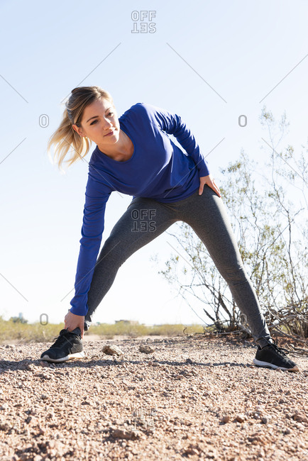 Female hiker exercising on field against clear sky during sunny day