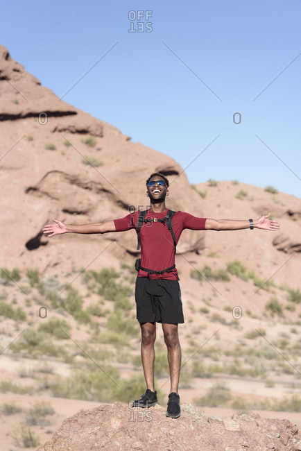 Male hiker with arms outstretched standing on rock against clear blue sky during sunny day
