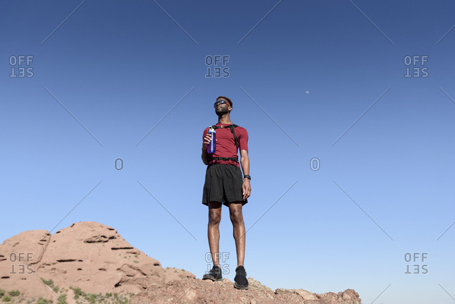 Low angle view of male hiker holding water bottle while standing on rock formation against clear blue sky
