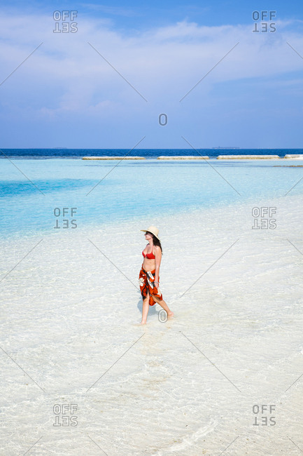 High angle view of woman wearing bikini and hat while walking at beach against sky during sunny day