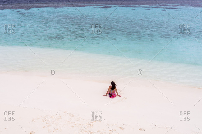 Rear view of woman sitting at sandy beach