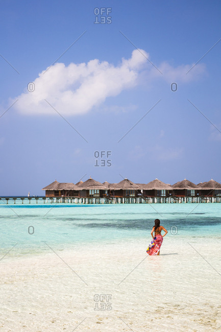 Rear view of woman with sarong standing at beach against blue sky during sunny day
