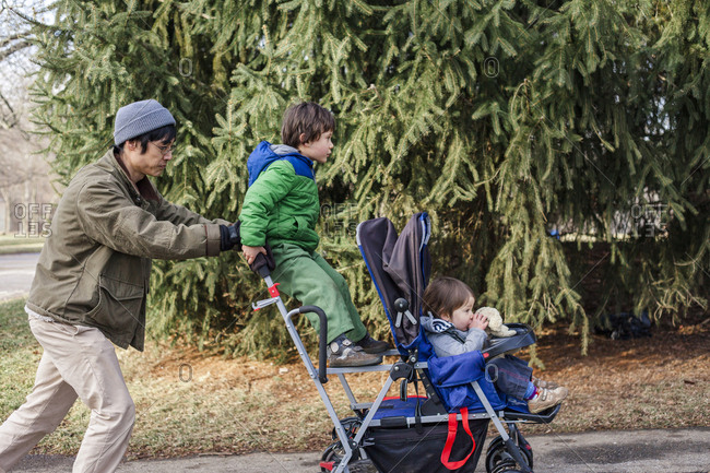 Side view of father pushing children sitting on baby stroller at park