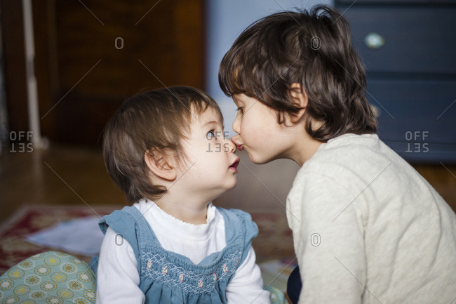 Close-up of brother kissing cute sister on nose while sitting at home