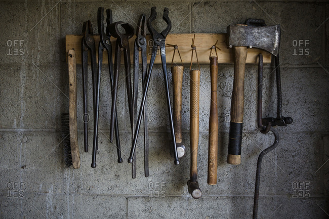 Close-up of work tools hanging on rack at blacksmith shop