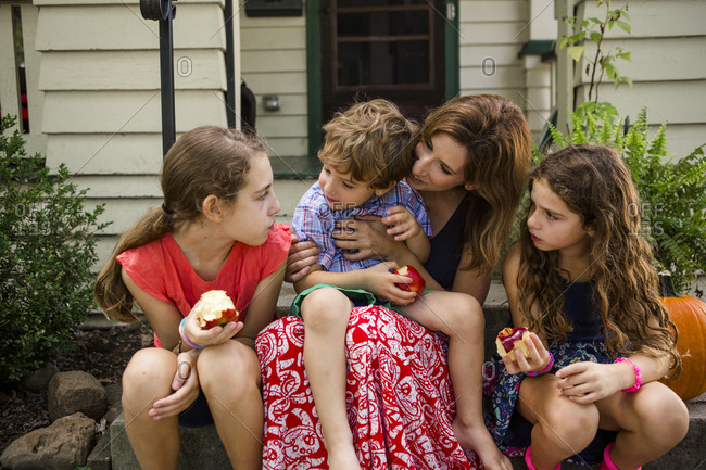 Mother talking with children eating apples while sitting on steps