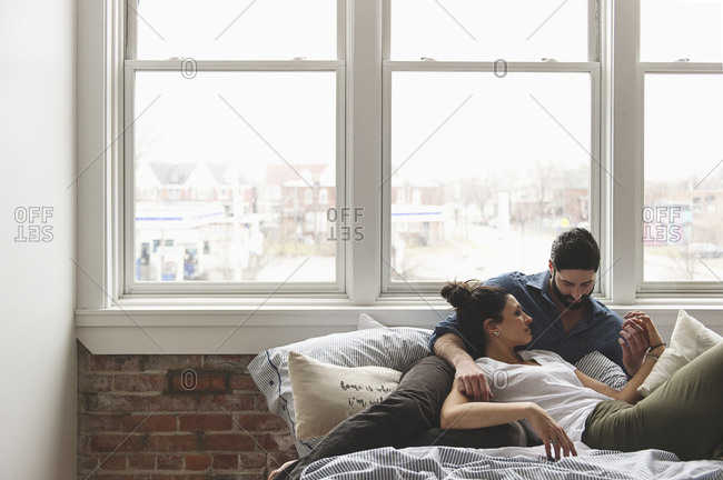 Romantic couple relaxing on bed by window at home