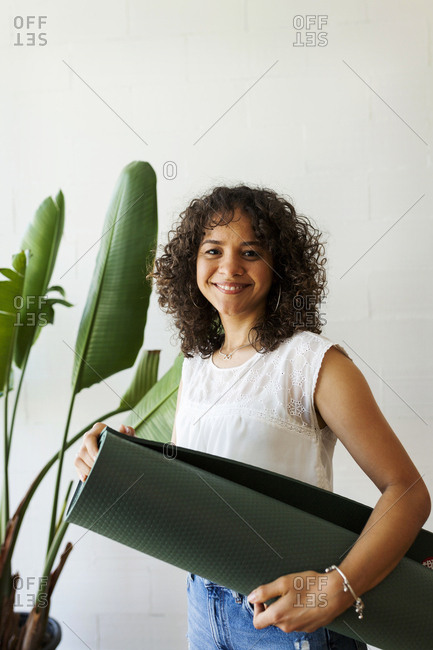 Portrait of smiling woman holding exercise mat while standing against wall in yoga studio
