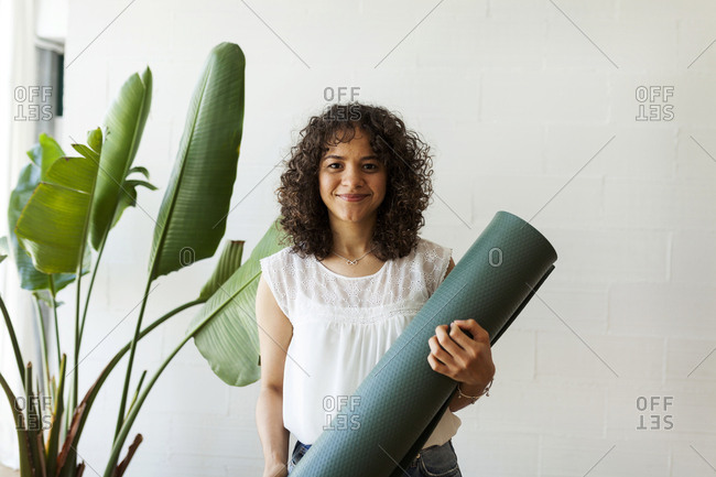 Portrait of woman holding exercise mat while standing against wall in yoga studio