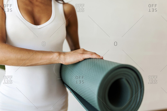 Midsection of woman holding exercise mat while standing against wall in yoga class