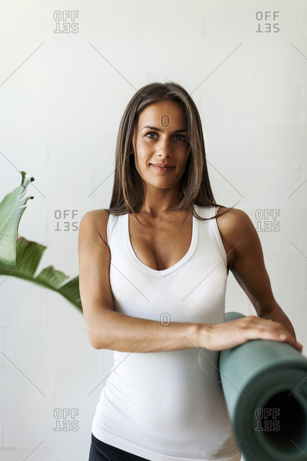 Portrait of woman holding exercise mat while standing against wall in yoga class